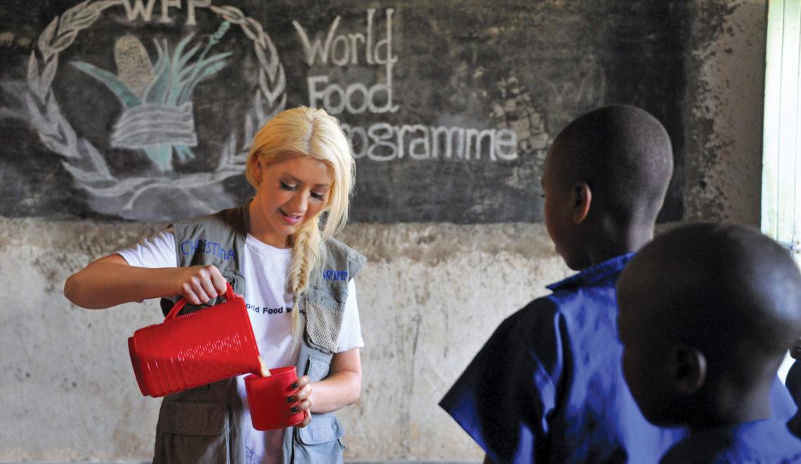 Volontaria del Programma Alimentare Mondiale assiste alcuni ragazzi assetati