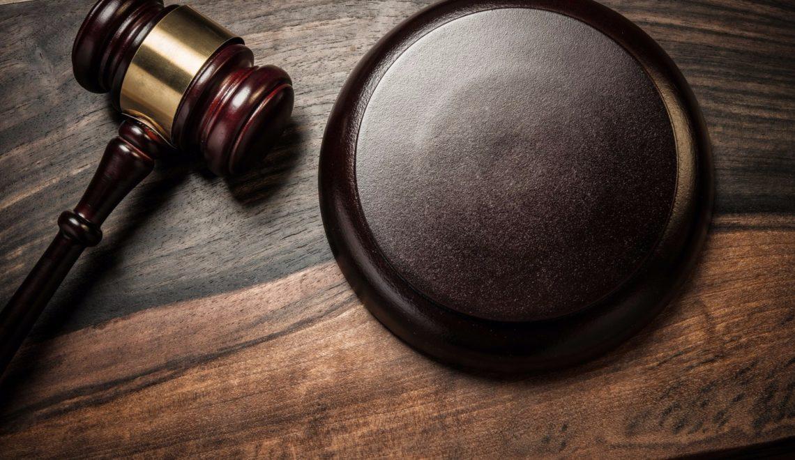 Martello giudiziario mostrato adagio su un tavolo in mogano.